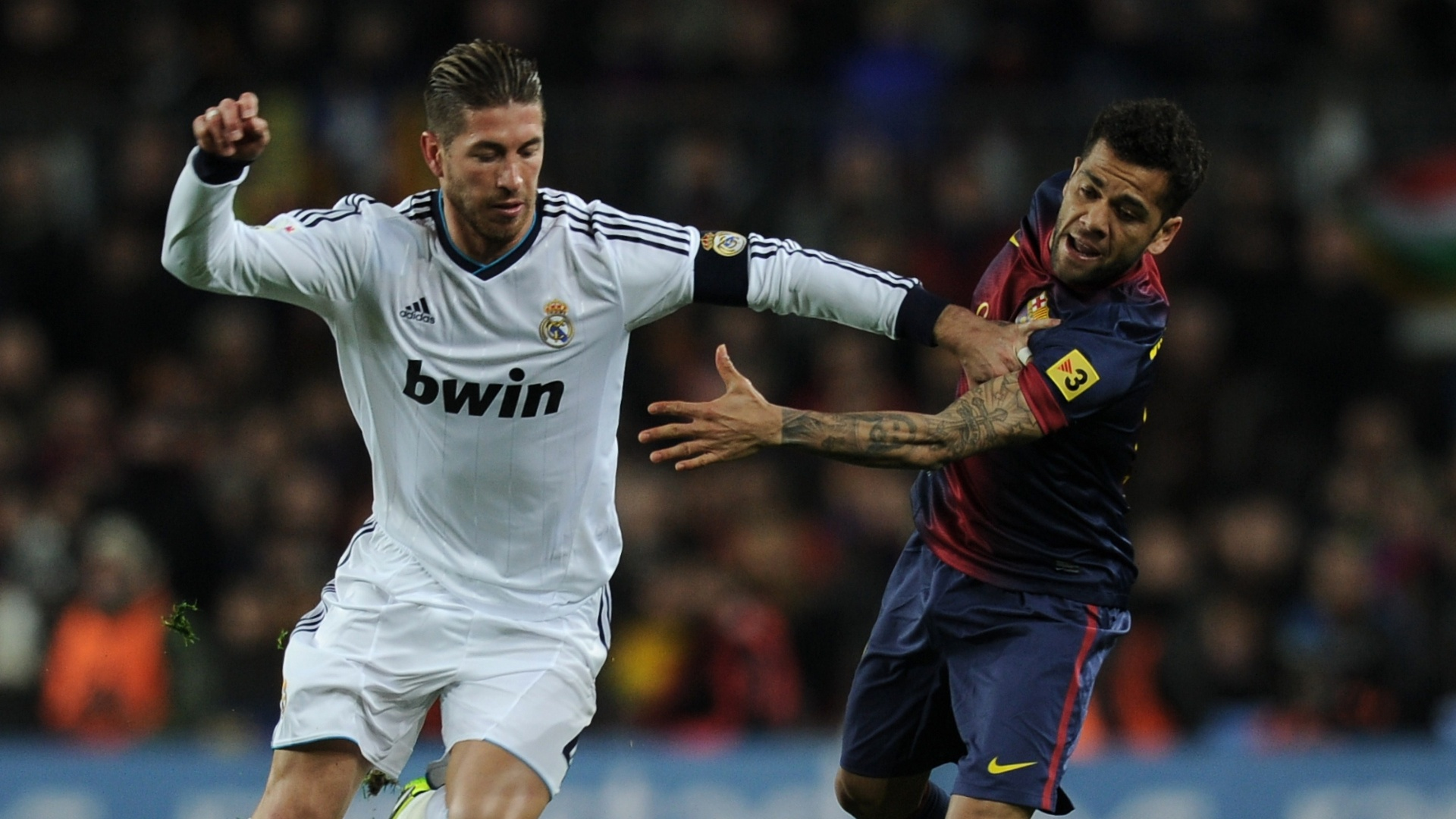 26.fev.2013 - Sergio Ramos (esq.), do Real Madrid, disputa bola com o brasileiro Daniel Alves (dir.), do Barcelona
