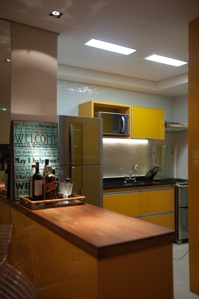 Na cozinha projetada pelas arquitetas Andrea Lucchesi e Carolina Razuk, os armários da marcenaria Santíssima Fé em laca na cor amarela dão vivacidade ao ambiente