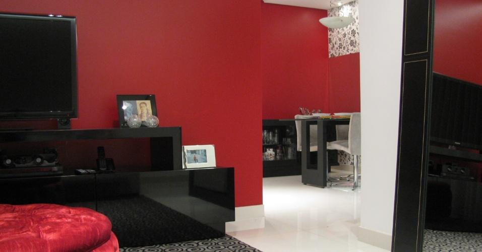 No projeto das designers de interiores Fabiana Visacro e Laura Santos, da VS Design, o uso da mesma cor (o vermelho) nas paredes das salas de estar e jantar funcionam como um elemento integrador para os dois espaços
