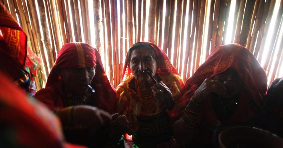 26.fev.2013 - Mulheres indígenas da tribo panamenha Guna fumam cachimbos e bebem uma bebida tradicional conhecida como Chi Cha durante celebração do 98º aniversário da revolução Kuna, na ilha de Ustupu, na costa caribenha do país. Em 1925, os índios Kuna, chamados hoje de Guna, lançaram uma rebelião, apoiada pelos EUA, por autonomia na região. Anos mais tarde foi criada oficialmente a reserva Kuna