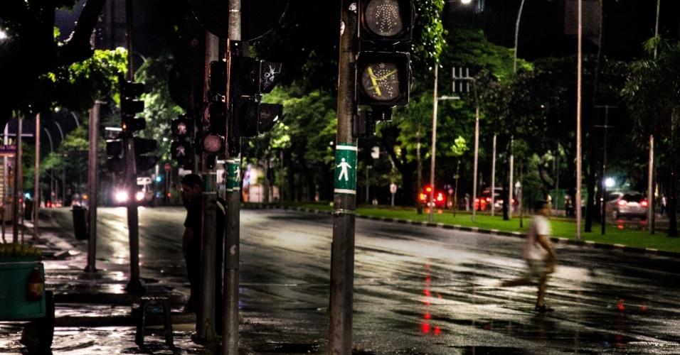 26.fev.2013 - Pedestre atravessa correndo a avenida Brigadeiro Faria Lima, no cruzamento com a avenida Rebouças, na zona oeste de São Paulo, onde todos os sem&#225