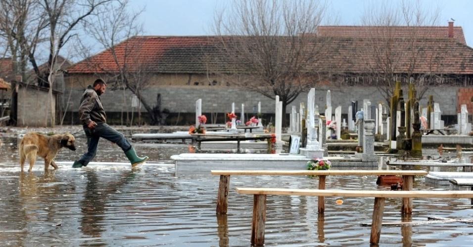 27.fev.2013 - 27.fev.2013 - Homem e cachorro caminham sobre túmulos em cemitério inundado, na vila de Monospitovo, na Macedônia. As chuvas dos últimos três dias na região inundaram campos e vilarejos, além de arruinar plantações