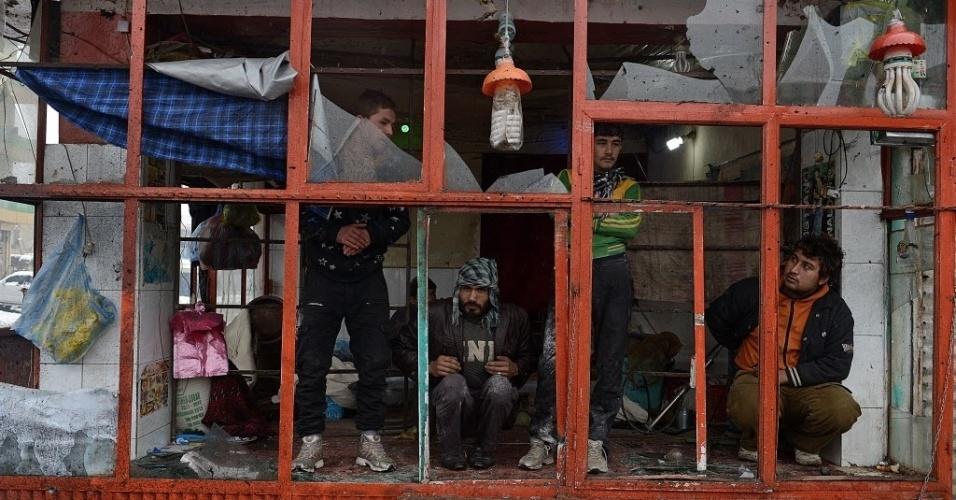 27.fev.2013 - Afegãos observam janelas de padaria destruídas, perto de local onde um ataque suicida contra um ônibus feriu seis pessoas, em Cabul, capital do país