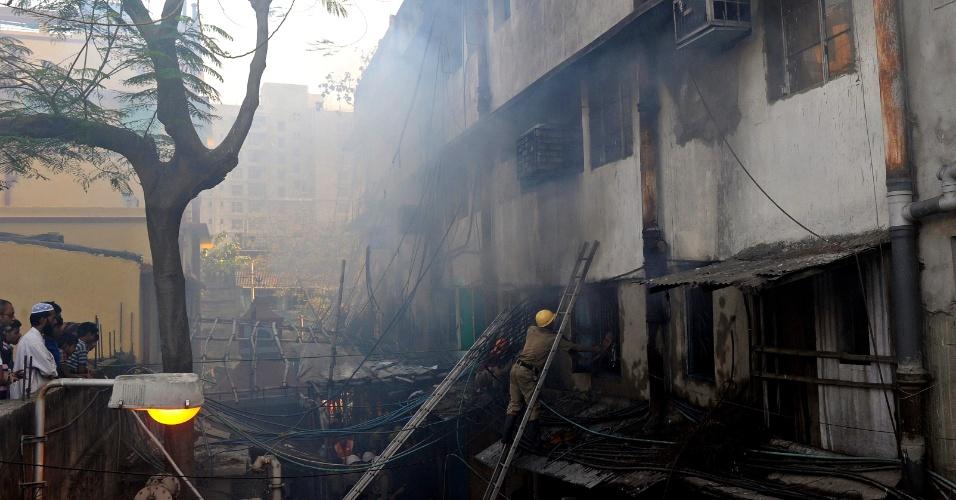 27.fev.2013 - Curiosos assistem a bombeiro combater incêndio no mercado Surya Sen, em Calcutá (Índia). O fogo atingiu os seis andares do edifício, que abriga um mercado de produtos ilegais ou contrabandeados, matando dezenas de pessoas
