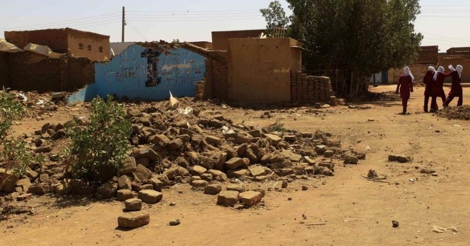 27.fev.2013 - Estudantes (fundo, à direita) circulam perto de igreja destruída no subúrbio de Cartum, capital do Sudão