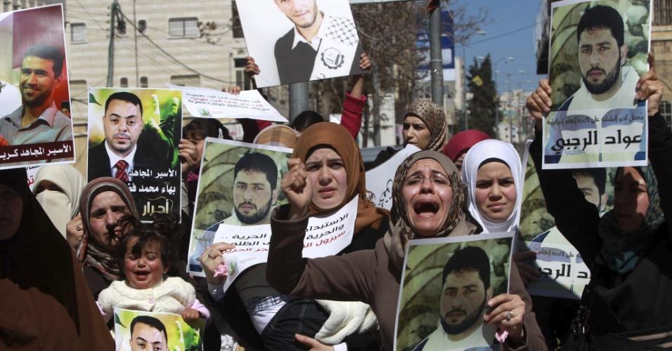 27.fev.2013 - Familiares de presos palestinos detidos em prisões de Israel mostram fotos dos parentes encarcerados durante uma manifestação em Ramallah, na Cisjordânia, nesta quarta-feira (27). No ato, os manifestantes expressaram solidariedade a todos os presos palestinos que mantém uma greve de fome nas cadeias israelenses