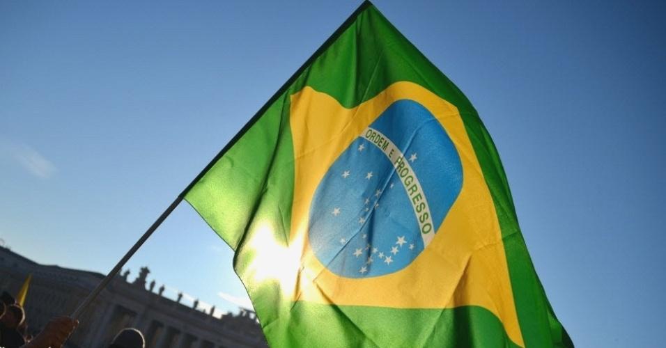 27.fev.2013 - Freira agita bandeira do Brasil na praça São Pedro, no Vaticano, às vésperas do último sermão do papa Bento 16. O líder da Igreja Católica renunciará oficialmente ao cargo na quinta-feira (28)