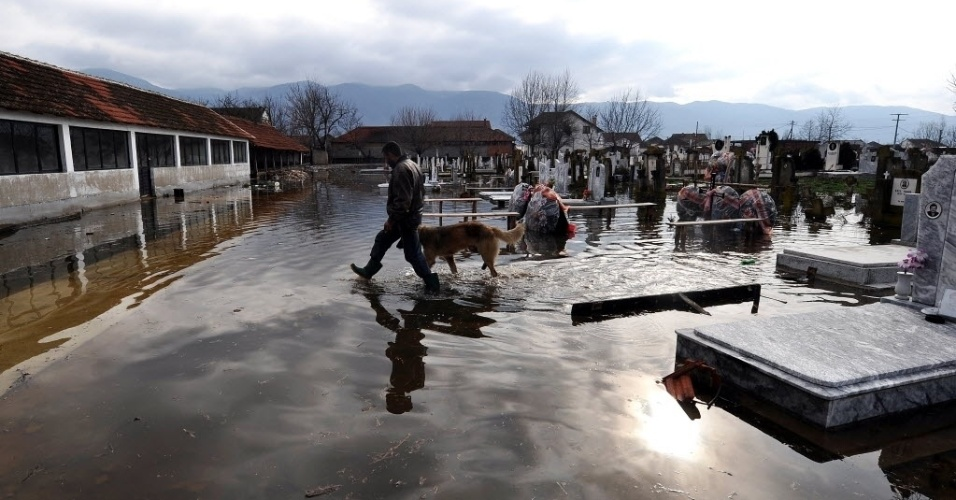 27.fev.2013 - Homem e cão caminham por cemitério inundado na vila de Monospitovo, na Macedônia, nesta quarta-feira (27). As chuvas torrenciais que atingiram o país nos últimos dias provocaram alagamentos e destruíram casas e plantações