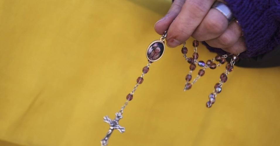 27.fev.2013 - Mulher segura cruz na praça de São Pedro, no Vaticano, onde o papa Bento 16 faz seu último discurso como líder da Igreja Católica
