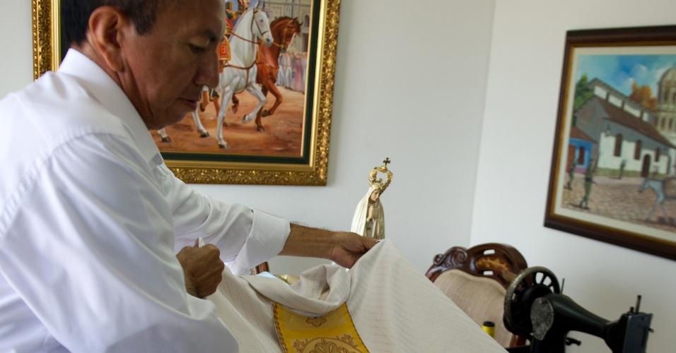 27.fev.2013 - O alfaiate Luis Abel Delgado trabalha na confecção de uma das roupas que serão usadas pelo sucessor de Bento 16, em sua oficina em Cali, na Colômbia. O alfaiate de 43 anos foi escolhido pelo Vaticano para fazer as roupas do próximo papa