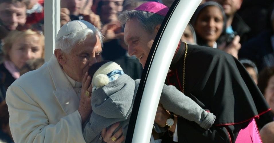 27.fev.2013 - Papa Bento 16 beija bebê ao chegar à praça de São Pedro, no Vaticano, para fazer seu último sermão como líder da Igreja Católica