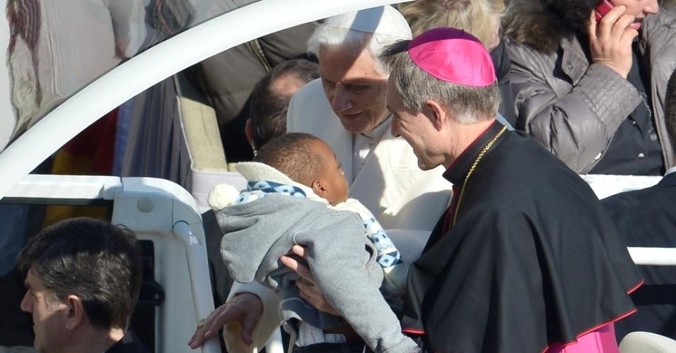 27.fev.2013 - Papa Bento 16 (centro) cumprimenta bebê ao chegar na praça de São Pedro, no Vaticano, onde fará seu último sermão como líder da Igreja Católica