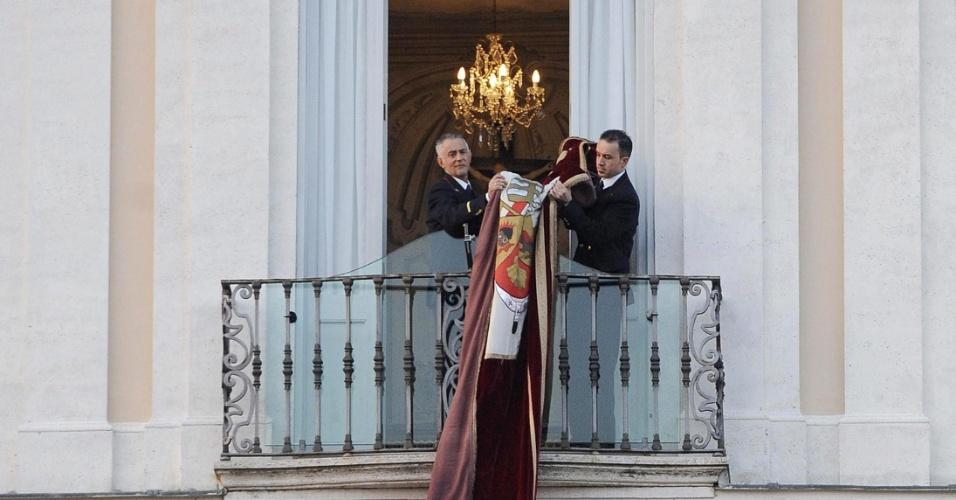 28.fev.2013 - Funcionários do Vaticano retiram a bandeira com o brasão de Bento 16 da sacada da residência de verão papal de Castel Gandolfo, no sul de Roma, onde o papa emérito viverá por dois meses antes de se mudar para um convento, no Vaticano. Nesta quinta-feira (28), Bento 16 deixou oficialmente o cargo