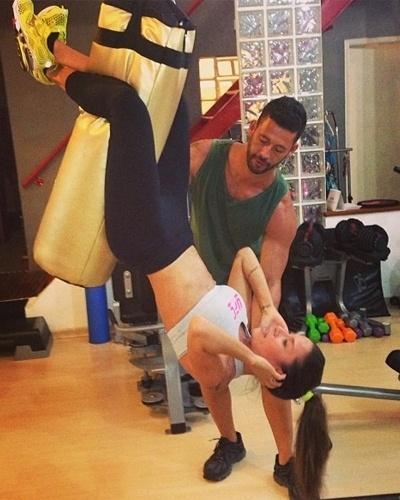 28.fev.2013 - Para definir ainda mais o abdome, Lizzi Benites faz um abdominal suspensa com a ajuda de um saco de boxe e seu personal trainer, Rogério Sthanke