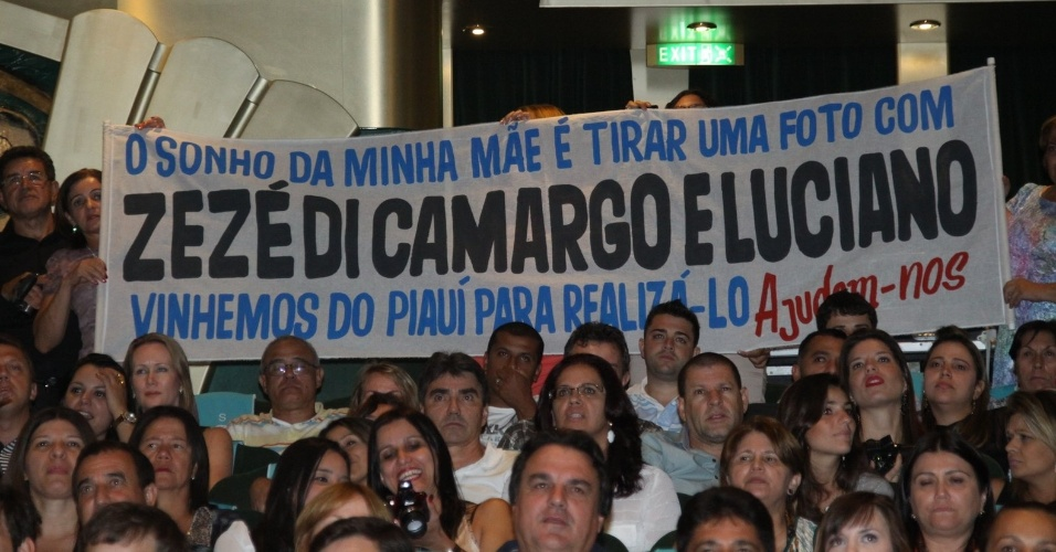 28.fev.2013 Fãs mostram faixa com pedido para tirar foto com a dupla Zezé di Camargo e Luciano durante a apresentação da dupla no cruzeiro
