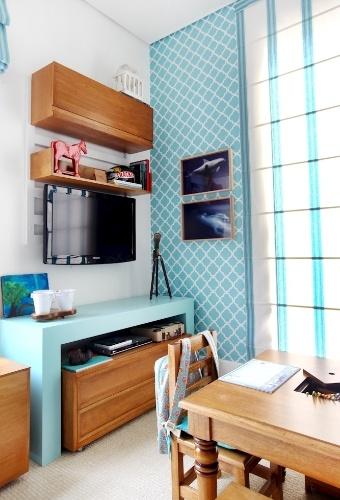 O tom claro de azul quebra a sobriedade dos móveis de madeira da