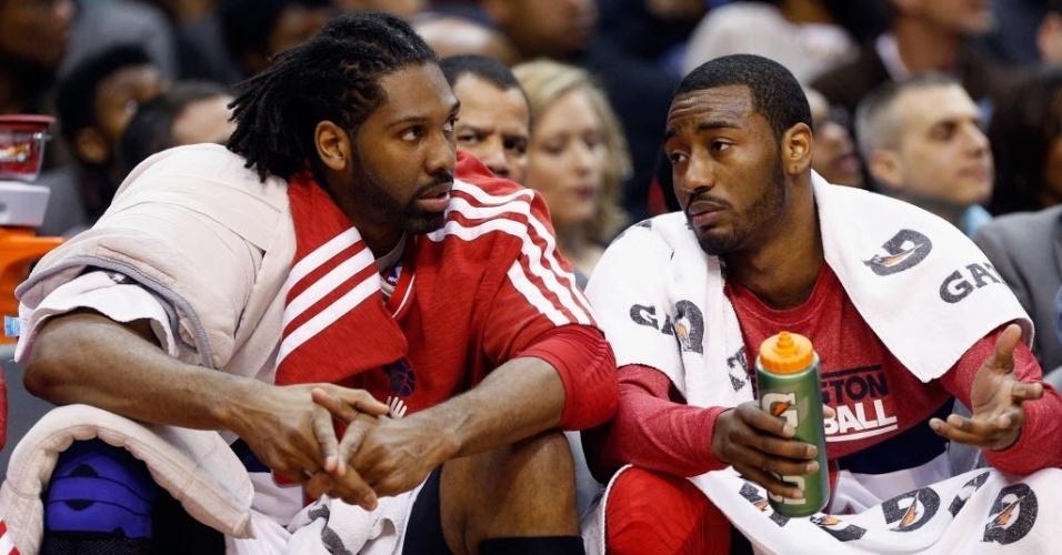 03.mar.2013 - O brasileiro Nenê (e) conversa com o armador John Wall durante a vitória dos Wizards sobre os 76ers