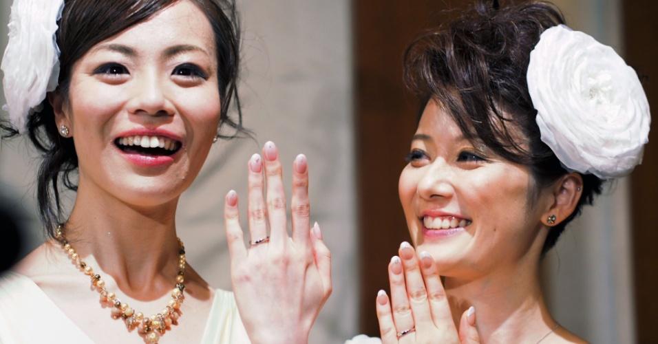 5.mar.2013 - Imagem divulgada nesta terça-feira (5) mostra as japonesas Koyuki Higashi (à esq.) e Hiroko (à dir.) sorrindo enquanto exibem as alianças durante sua cerimônia de casamento, realizada no parque temático da Disney, em Tóquio, na sexta-feira (1º). Elas se tornaram o primeiro casal gay a se casar no resort da Disney japonesa, embora a união não seja legalmente reconhecida pelo país asiático. Ambas usaram vestidos de noiva, apesar de inicialmente ter sido exigido que uma delas vestisse trajes masculinos