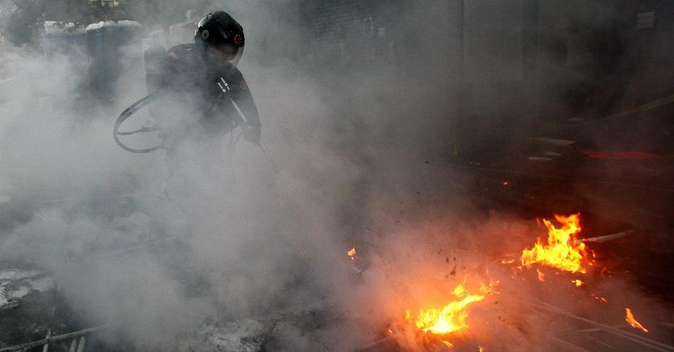 5.mar.2013 - Bombeiro apaga objetos incendiados em rua de Caracas, em acampamento de estudantes oposicionistas que haviam se acorrentado em protesto por informações sobre a saúde do presidente Hugo Chávez. O fogo foi supostamente ateado por partidários do presidente, após o anúncio de sua morte, nesta terça-feira (5). Os manifestantes oposicionistas deixaram o local correndo. Não há infromações sobre feridos