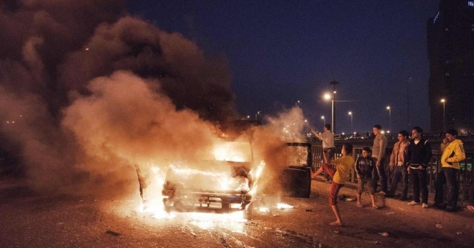5.mar.2013 - Manifestantes observam carro de polícia em chamas em área do Cairo, capital do Egito. Em várias áreas do país há protestos. Nesta terça-feira (5), na cidade de Port Said, a polícia disparou tiros para o alto e lançou bombas de gás lacrimogêneo durante confrontos com centenas de manifestantes