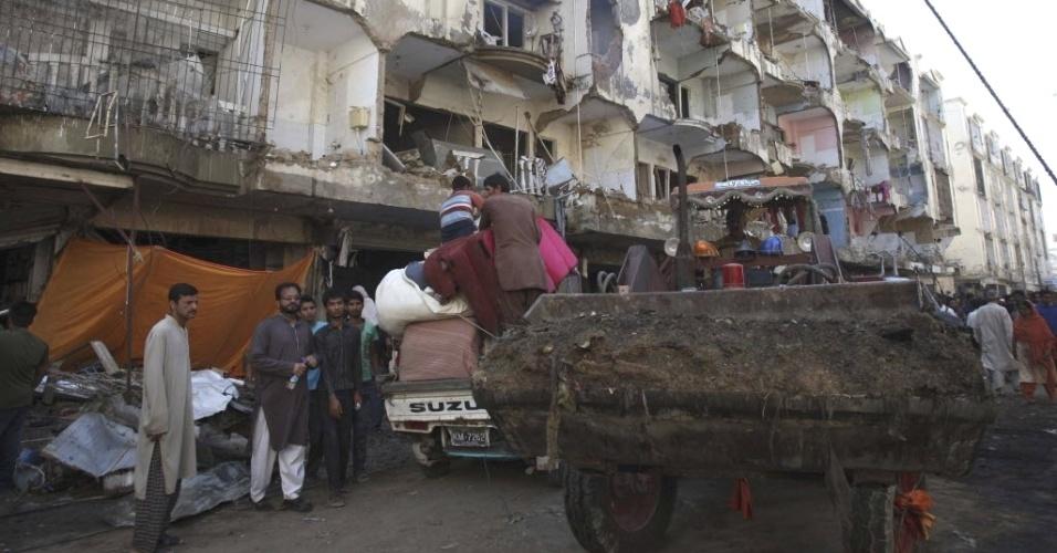 5.mar.2013 - Moradores resgatam seus pertences dos escombros de prédio atingido por um atentado em Karachi, no Paquistão