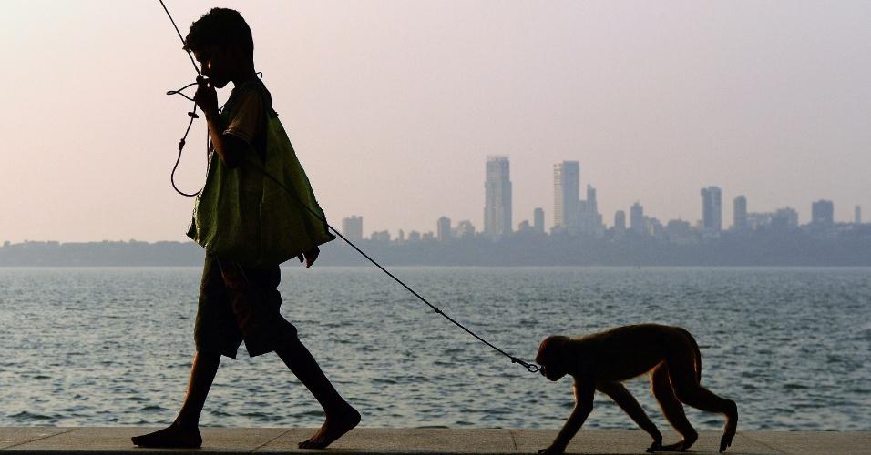 5.mar.2013 - O garoto Suraj, 11, caminha com seu macaco de estimação antes de apresentar um show de acrobacias com a participação do animal, às margens do mar da Árabia, em Mumbai (Índia). Suraj ganha em média US$ 2 (cerca de R$ 4) por dia com apresentações para os turistas