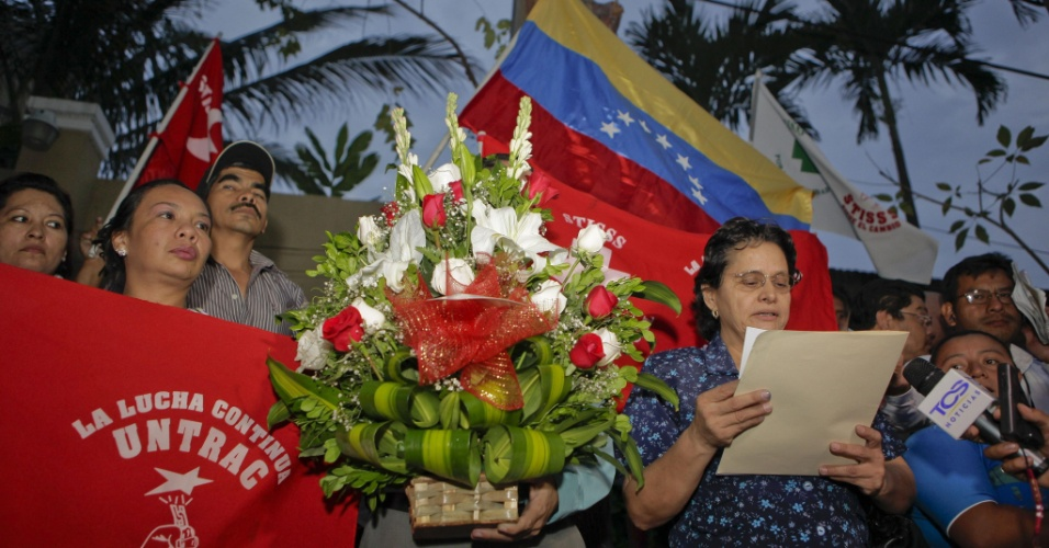 """5.mar.2013 - Simpatizantes do presidente venezuelano, Hugo Chávez, se reúnem em homenagens em frente à embaixada da Venezuela em San Salvador, El Salvador, nesta terça-feira. Mais cedo, o presidente de El Salvador, Mauricio Funes, expressou condolências ao chamar Chávez de """"grande líder"""" e """"patriota"""""""