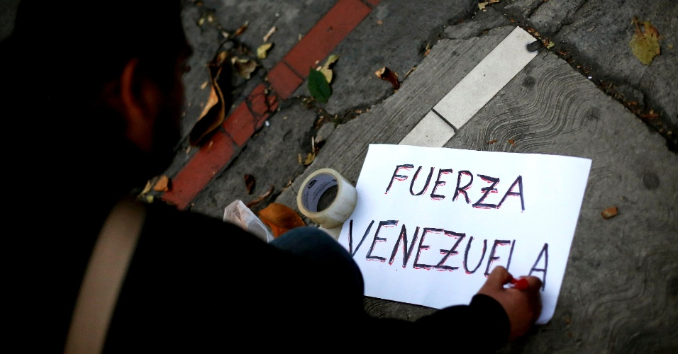 """5.mar.2013 - Apoiador de Hugo Chávez escreve um cartaz onde se lê, em castelhano: """"Força, Venezuela"""", diante da embaixada venezuelana na Cidade do México. Chávez, polarizador de opiniões, visto como herói e como ditador, morreu hoje aos 58 anos, em Caracas"""