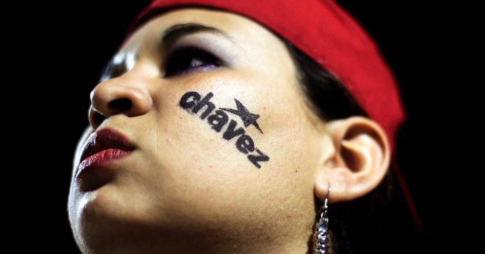 5.mar.2013 - Apoiadora do presidente venezuelano Hugo Chávez leva seu nome escrito no rosto durante vigília realizada em praça de San Salvador (El Salvador). Chávez morreu hoje aos 58 anos, vítima de um câncer com o qual convivia há um ano e meio