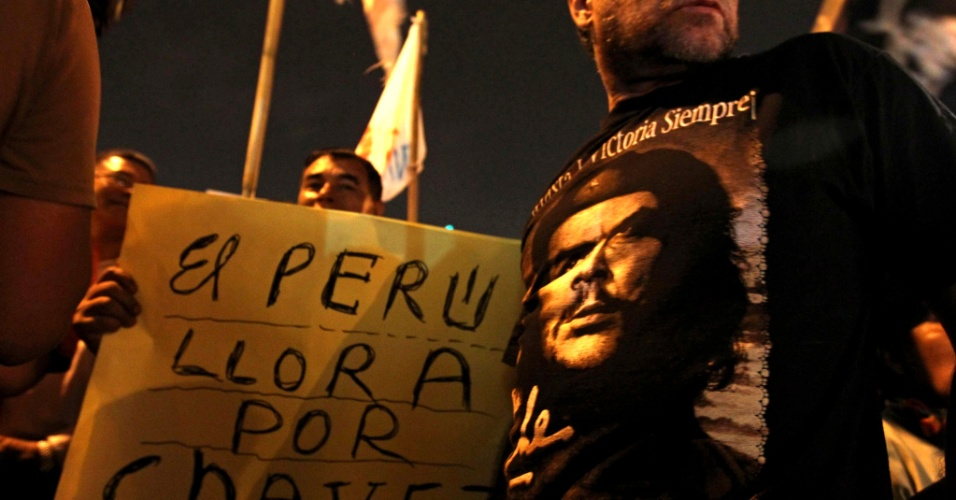 """5.mar.2013 - Apoiadores de Hugo Chávez se reúnem diante da embaixada venezuelana em Lima (Peru). No cartaz, lê-se """"Peru chora por Chávez"""". Chávez, polarizador de opiniões, visto como herói e como ditador, morreu hoje aos 58 anos, em Caracas"""