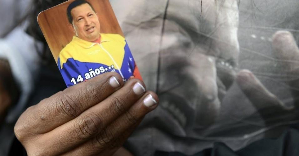 6.mar.2013 - Apoiador do presidente da Venezuela, Hugo Chávez, exibe santinho de Hugo Chávez em frente ao Hospital Militar Dr. Carlos Arvelo, em Caracas, onde o mandatário morreu na terça-feira (5). Chávez, morto aos 58 anos, lutava contra um câncer na região pélvica