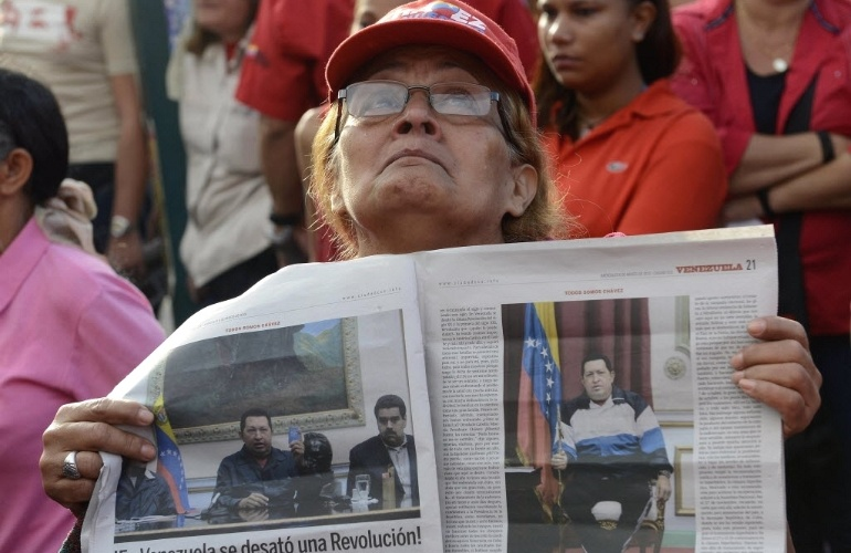 6.mar.2013 - Apoiadora do presidente da Venezuela, Hugo Chávez, exibe jornal em frente ao Hospital Militar Dr. Carlos Arvelo, em Caracas, onde o mandatário morreu na terça-feira (5). Chávez, morto aos 58 anos, lutava contra um câncer na região pélvica