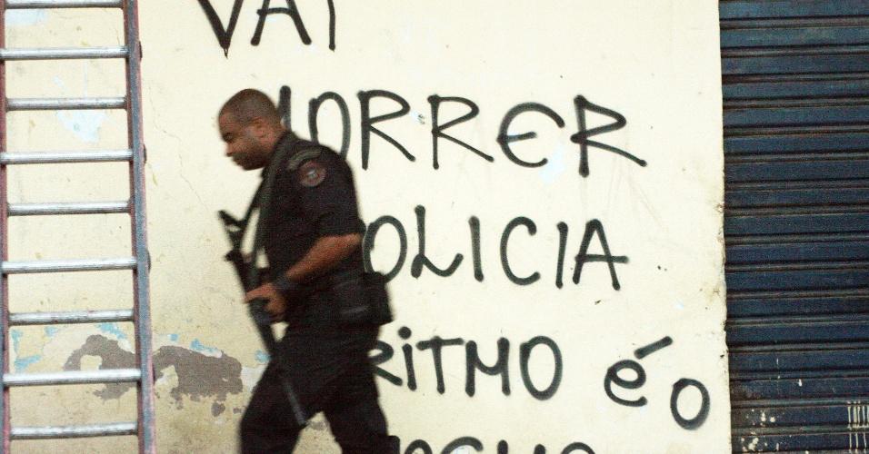 6.mar.2013 - Em imagem deste domingo (3), policial caminha diante de pichação na favela do Caju, no Rio de Janeiro, após a ocupação da comunidade. Segundo a secretaria de Segurança Pública, as forças policiais levaram apenas 25 minutos para tomar o controle da região