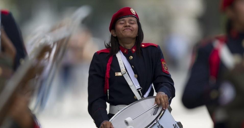 6.mar.2013 - Emocionada, integrante da banda de guerra do Exército da Venezuela ensaia para a caravana que acompanhará o cortejo do presidente Hugo Chávez, na praça onde fica o Monumento à Nação, em Caracas. O presidente da Venezuela morreu na terça-feira (5), aos 58 anos, vítima de um câncer na região pélvica. Desde às 6h em Caracas (8h de Brasília), as Forças Armadas do país disparam 21 tiros de canhão a cada hora, até que o corpo de Chávez seja enterrado