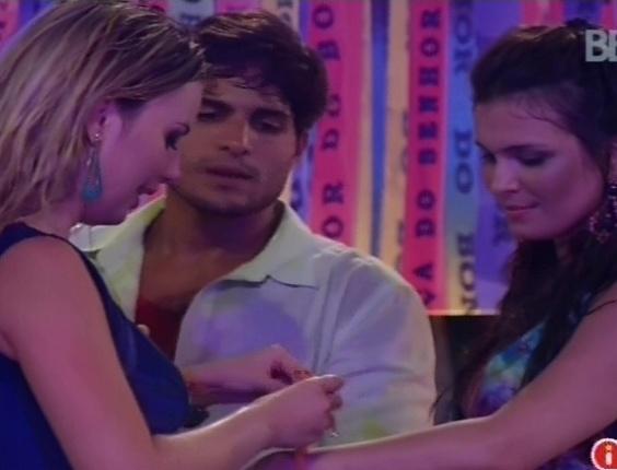 6.mar.2013 - Fernanda amarra fitinha do senhor do Bonfim no braço de Andressa