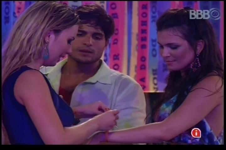 6.mar.2013 - Fernanda amarra fitinha do senhor do Bonfim no braço de Kamilla