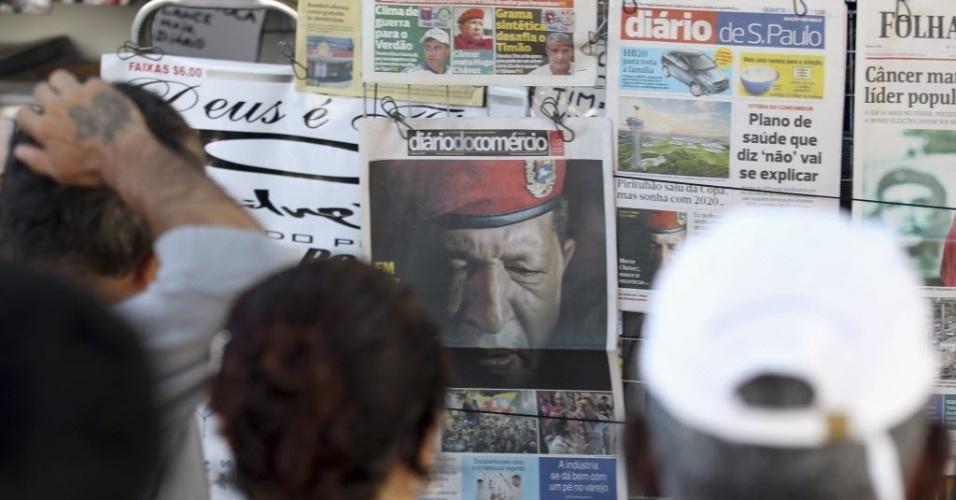 6.mar.2013 - Moradores de São Paulo se aglomeram em frente de banca de jornal da capital paulista, onde as manchetes dos principais jornais são a morte de Hugo Chávez. O presidente da Venezuela morreu na terça-feira (5), aos 58 anos, vítima de um câncer na região pélvica