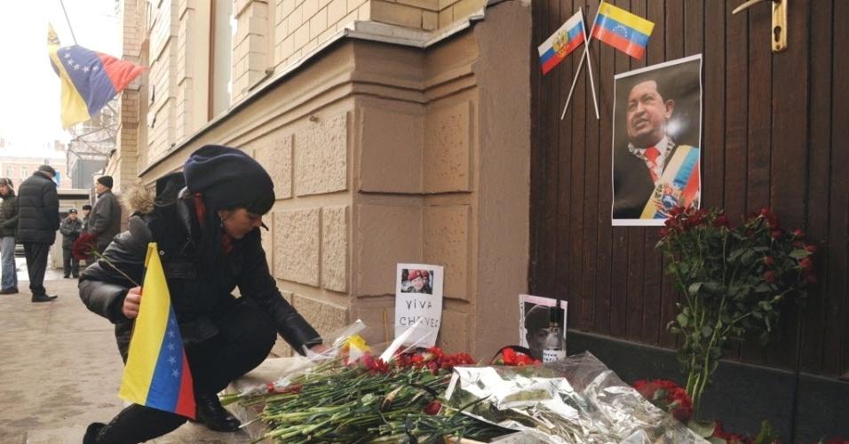 6.mar.2013 - Mulher põe flores em memorial montado na entrada da embaixada da Venezuela em Moscou, um dia após a morte do presidente Hugo Chávez. O mandatário venezuelano morreu na terça-feira (5), aos 58 anos, vítima de um câncer na região pélvica