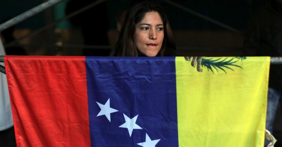 6.mar.2013 - Mulher segura uma bandeira venezuelana em frente ao consulado do país em Barcelona, Espanha, nesta quarta-feira. Ela e um grupo de apoiadores do regime bolivariano fazem homenagens ao presidente da Venezuela, Hugo Chávez, morto nesta terça-feira (4), em decorrência de um câncer