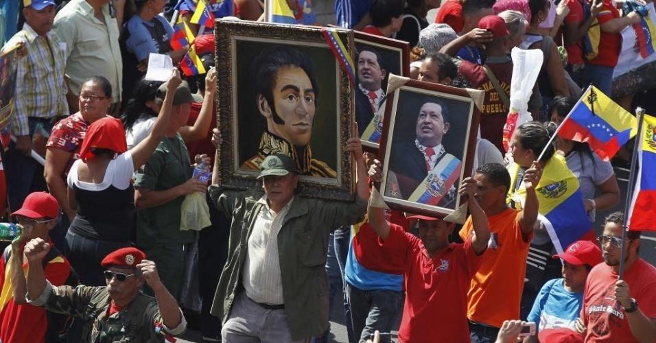 6.mar.2013 - Multidão acompanha cortejo fúnebre de Hugo Chávez com retratos do presidente da Venezuela e do herói da independência Simón Bolívar, nesta quarta-feira (6), na capital Caracas. Chávez morreu ontem (5), aos 58 anos, vítima de um câncer na região pélvica