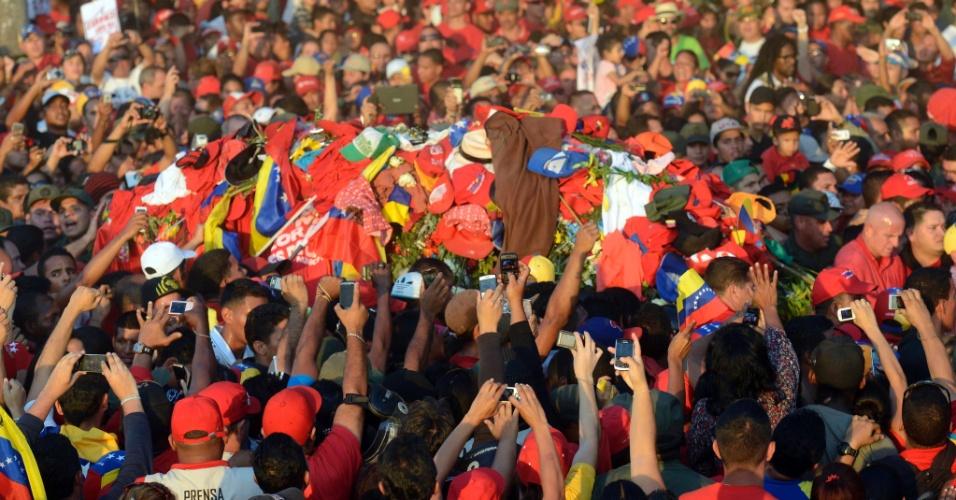 6.mar.2013 - Multidão se aproxima de caixão com o corpo do presidente venezuelano, Hugo Chávez, em sua chegada à Academia Militar, em Caracas, nesta quarta-feira. Chávez morreu na tarde desta terça-feira (5), vítima de câncer. Ele estava há 14 anos no poder