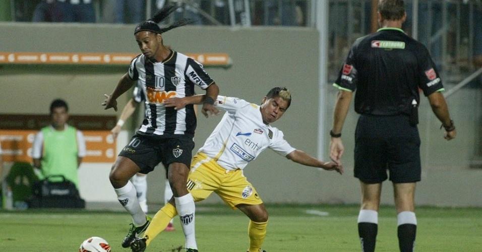07.mar.2013 - Ronaldinho, do Atlético-MG, tenta escapar da marcação do The Strongest em jogo válido pela Libertadores, na Arean Independência