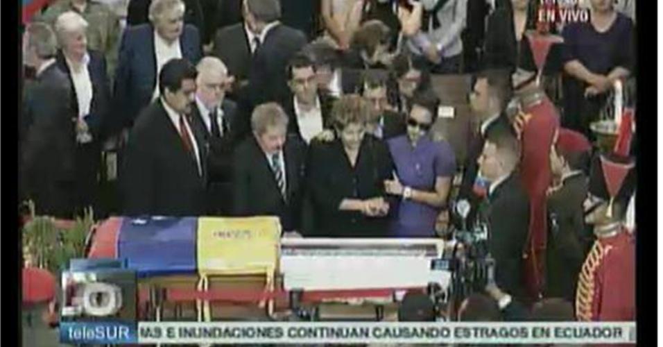 7.mar.2013 - A presidente Dilma Rouseff (de preto, à dir.) olha para o caixão com o corpo do presidente venezuelano Hugo Chávez. Na frente, da esquerda para a direita aparecem o presidente interino da Venezuela, Nicolás Maduro, e o ex-presidente Luiz Inácio Lula da Silva