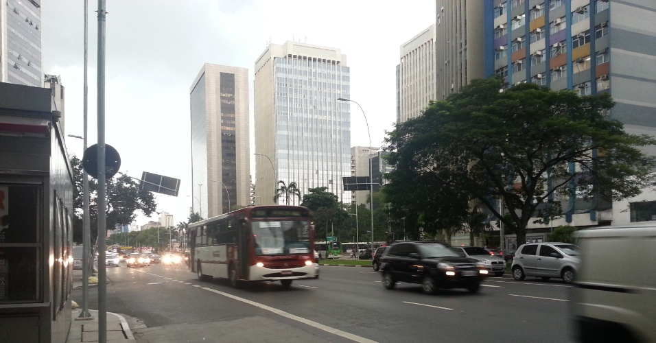 7.mar.2013 - Às 14h desta quinta-feira (7), nuvens de chuva fazem veículos circular com faróis ligados na avenida Faria Lima céu, zona oeste de São Paulo