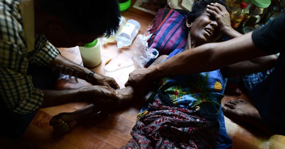 7.mar.2013 - Voluntário administra remédio em infusão intravenosa em uma paciente portadora de HIV, em clínica na periferia de Yangon, maior cidade de Mianmar. A pequena clínica é refúgio para cerca de 300 pacientes que não recebem tratamento no sistema público de saúde