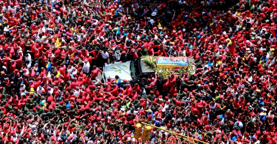7.mar.2013 - Em imagem desta quarta-feira (6) e divulgada hoje pela assessoria de imprensa do palácio presidencial da Venezuela, multidão cerca o carro que leva o caixão com corpo do presidente Hugo Chávez pelas ruas de Caracas