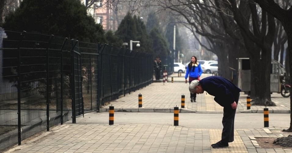 7.mar.2013 - Idoso faz saudação oriental típica em frente à embaixada da Venezuela em Pequim, na China. Hugo Chávez, presidente da Venezuela, morreu na terça-feira (5), aos 58 anos, vítima de um câncer na região pélvica