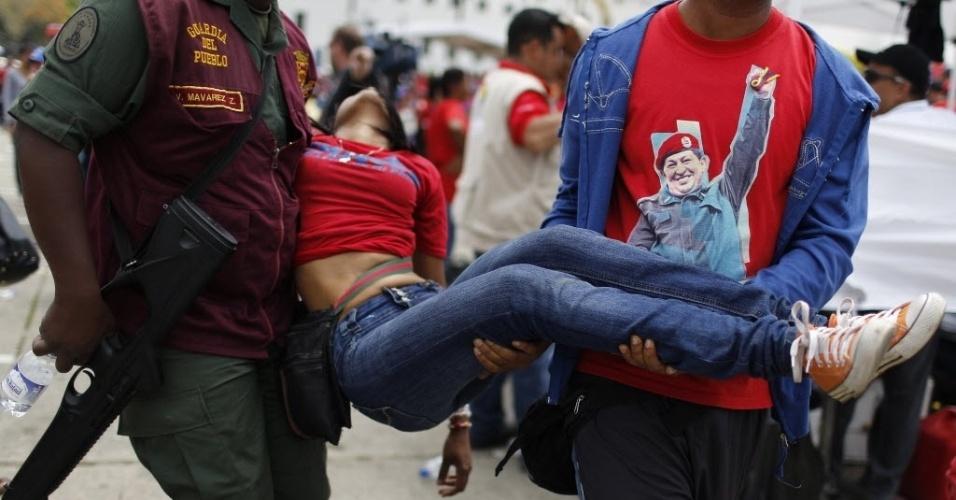 7.mar.2013 - Jovem é atendida após desmaiar no meio da multidão que aguarda para ver o corpo do presidente da Venezuela, Hugo Chávez, que está sendo velado na Academia Militar, em Caracas. A espera na fila para dar adeus a Chávez dura cerca de 12 horas, e muitos venezuelanos passaram mal com o calor que faz na capital do país