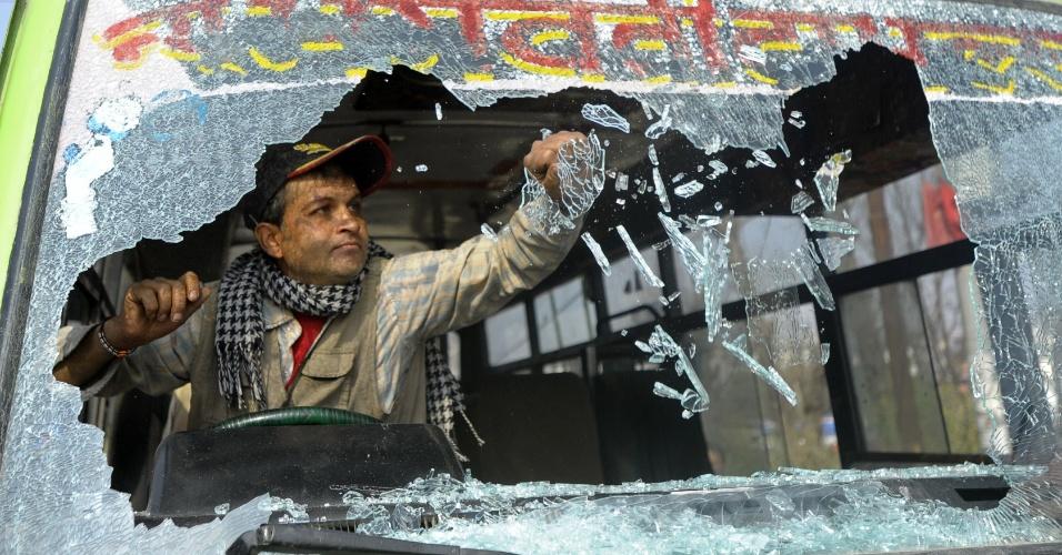 7.mar.2013 - Motorista de ônibus retira restos de vidro quebrado após seu veículo ter sido atacado nesta quinta-feira (7) durante greve geral em Katmandu, capital do Nepal