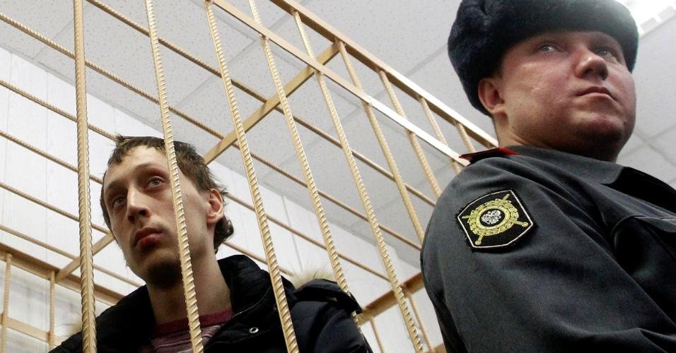 7.mar.2013 - Pavel Dmitrichenko, à esquerda, bailarino acusado de atacar com ácido o diretor artístico do balé Bolshoi assiste, da cela do réu, a audiência sobre o caso, em corte de Moscou